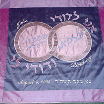 "Removable Chuppah Panel (detail) - The Hebrew and English names of the couple are incorporated into the double-ring design, along with the traditional ""I am my beloved's, and my beloved is mine"" quote."